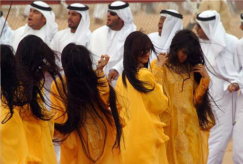 Young girls participating in Al-Razfa, dancing and swinging their long hair in tune to the strong beat of music, UAE