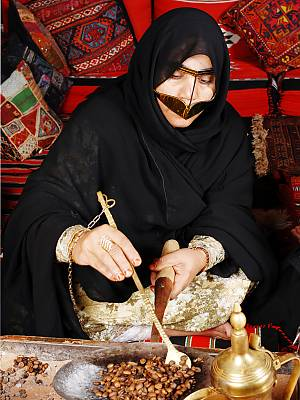 An Emarati woman wearing the traditional burqa (face mask) roasting  Arabic coffee beans using Al-Mehmas and Al-Migla (a copper stir and a pan, tools for roasting Arabic coffee) while participating in an Arabic coffee making competition.