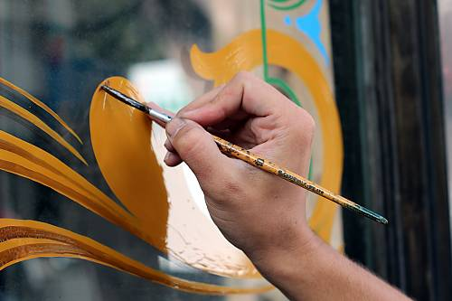 Painting a store window: after the plain colours are done, the 'yapán' (coloured varnish) is added, in order to give volume to the painting
