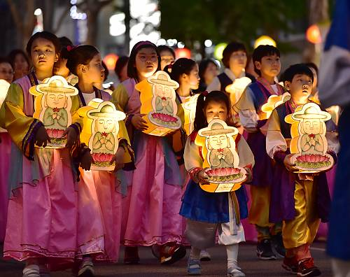 Children are parading with holding buddha-shaped lanterns