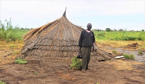 A South Sudanese man in front of his house destroyed by flooding in Kangu/ Kujonok